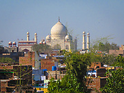 The Taj Mahal across the city rooftops. It is an ivory-white marble mausoleum on the southern bank of the river Yamuna.