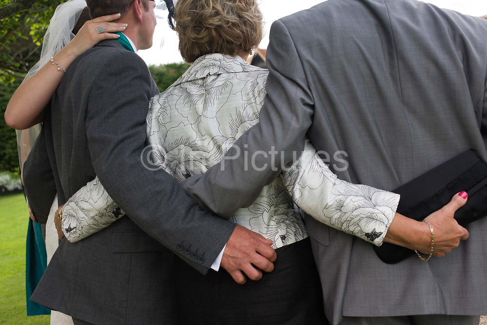 Interlocked arms and hands as a family portrait is recorded after a civil wedding ceremony in Essex, England. The family members include the bride herself, the groom, the bride's mother and her husband - the bride's father all stand with their backs to the viewer and stand in a close relationship of affection and bond. This European wedding has taken place inside a covered Orangery at a private wedding and event venue. Rather than marrying in a religious context, the happy couple have preferred to tie the knot in this popular setting for a non-church meaning.