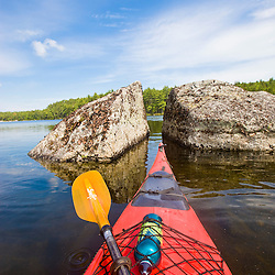 The bow of a kayak points at two large boulders in Branch Lake in Ellsworth, Maine.