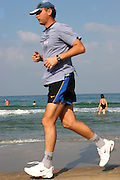 a young man jogging on the beach, Tel Aviv Israel October 2005