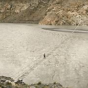 Shortly before reaching Passu village, a trekker walks along a hanging bridge across the Hunza River.