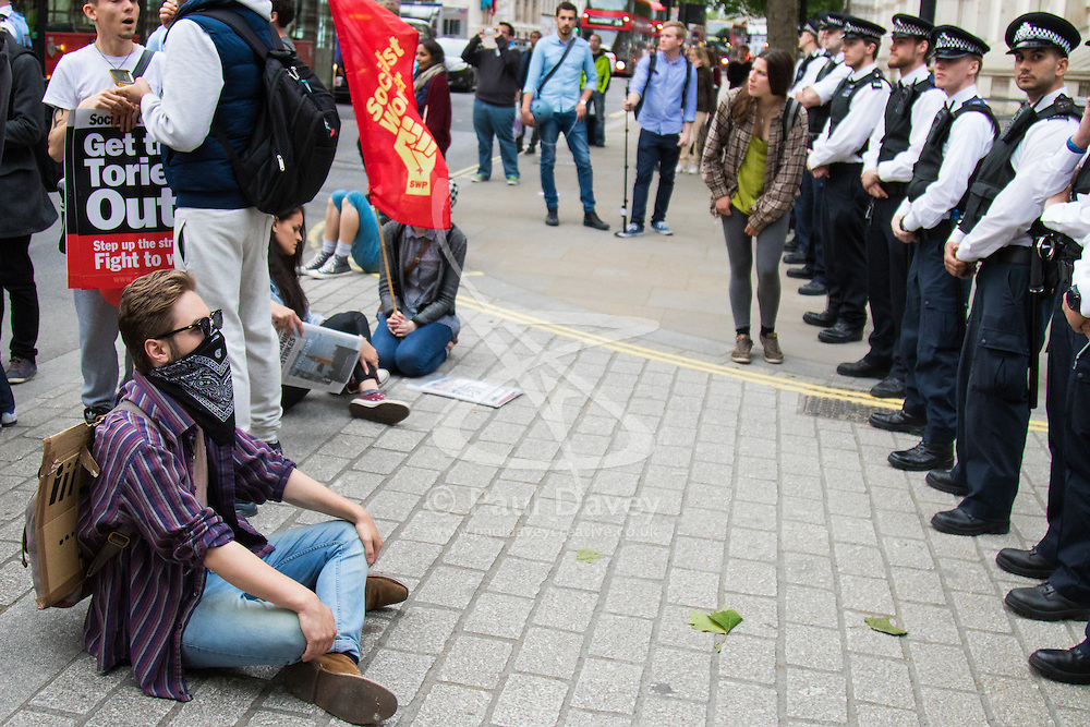 London, May 27th 2015. A protester sits in front of police lines protecting the entrance to Downing Street during demonstrations  against the Tories' ongoing campaign of austerity on the day the Queen delivered her speech to Parliament