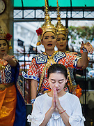 22 AUGUST 2015 - BANGKOK, THAILAND: People pray as Thai dancers perform behind them at the Erawan Shrine. Traditionally, people who want to make merit pay the dancers to perform while they pray. Erawan Shrine in Bangkok reopened Wednesday, August 19, after more than 20 people were killed and more than 100 injured in a bombing at the shrine Monday, August 17, 2015. The shrine is a popular tourist attraction in the center of Bangkok's high end shopping district and is an important religious site for Thais. No one has claimed responsibility for the bombing.             PHOTO BY JACK KURTZ