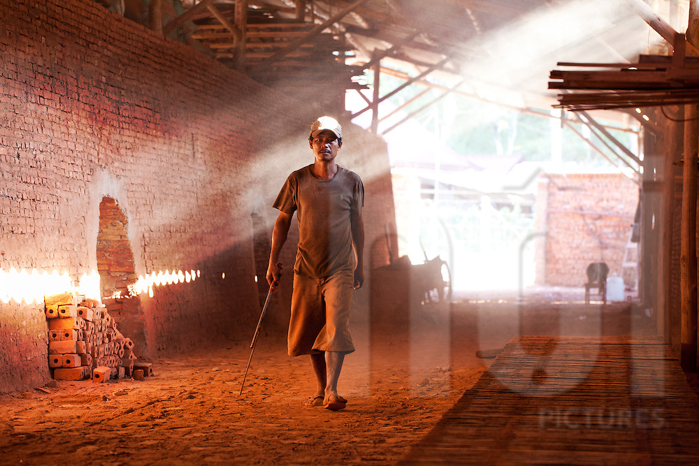 A man walks in a brick factory with the sun hitting the dred dust. Laos, Asia
