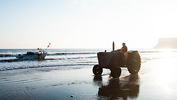 © Licensed to London News Pictures. <br /> 24/04/2015. <br /> <br /> Saltburn, United Kingdom<br /> <br /> Malcolm Jefferson heads up the beach to park his tractor after launching his boat, Ellen before joining his brother Lesley on board and heading out to lay lobster pots. <br /> Malcolm runs the last remaining commercial fishing boat out of Saltburn.<br /> <br /> <br /> Photo credit : Ian Forsyth/LNP