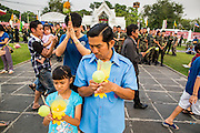 "25 FEBRUARY 2013 - BANGKOK, THAILAND:   A man and his daughter pray in front of a group of Thai soldiers at Wat Benchamabophit Dusitvanaram (popularly known as either Wat Bencha or the Marble Temple) on Makha Bucha Day. Makha Bucha is a Buddhist holiday celebrated in Myanmar (Burma), Thailand, Cambodia and Laos on the full moon day of the third lunar month (February 25 in 2013). The third lunar month is known in Thai is Makha. Bucha is a Thai word meaning ""to venerate"" or ""to honor"". Makha Bucha Day is for the veneration of Buddha and his teachings on the full moon day of the third lunar month. Makha Bucha Day marks the day that 1,250 Arahata spontaneously came to see the Buddha. The Buddha in turn laid down the principles his teachings. In Thailand, this teaching has been dubbed the 'Heart of Buddhism'.    PHOTO BY JACK KURTZ"