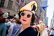 New York, NY - April 16, 2017. A woman in round sunglasses wears a jaunty straw hat with blue feather accents at New York's annual Easter Bonnet Parade and Festival on Fifth Avenue.