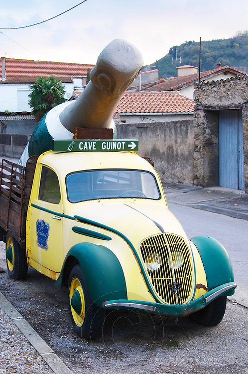 Cave Guinot. Yellow and Green old Peugeot 202 car with a gigantic Limoux bottle serving as an advertisement publicity for the winery. Limoux. Languedoc. France. Europe. Bottle.