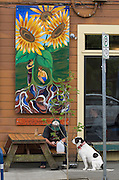 A man and his dog sit outside a coffee shop in front of  a mural depicting people and sunflowers at a coffee shop in north Portland, Oregon.