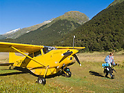 A small yellow Skywagon airplane drops off a hiker at Siberia Valley airstrip in Mount Aspiring National Park in the Southern Alps, South Island, New Zealand. In 1990, UNESCO honored Te Wahipounamu - South West New Zealand as a World Heritage Area.