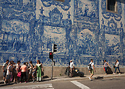 Portuguese citzens walk along the Rua de Fernandes Tomas where Azulejo tiles on the exterior of Capela Das Almas are seen above, on 19th July, in Porto, Portugal. The Churchs magnificent panels depict scenes from the lives of various saints, including the death of St Francis and the martyrdom of St Catherine. Eduardo Leite painted the tiles in a classic 18th-century style, though they actually date back only to the early 20th century.