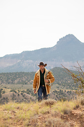 cowboy in a sheepskin coat walking on a mountain range in the desert