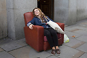 Woman takes the weight off her feet to relax in an armchair which has been abandoned on the street in Earls Court, London, UK. Laughing at the weirdness of the street scene.