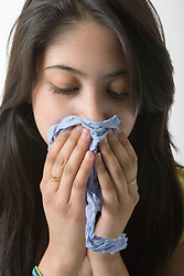 Portrait of a teenage girl blowing her nose,