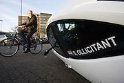 Een man fietst voorbij een geparkeerde Carver One. De driewielige Nederlandse auto kantelt.