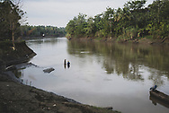 Two American women visiting the village of Yar, in the East Sepik Province of Papua New Guinea, talk together while standing in the Keram River to bathe. (June 21, 2019)