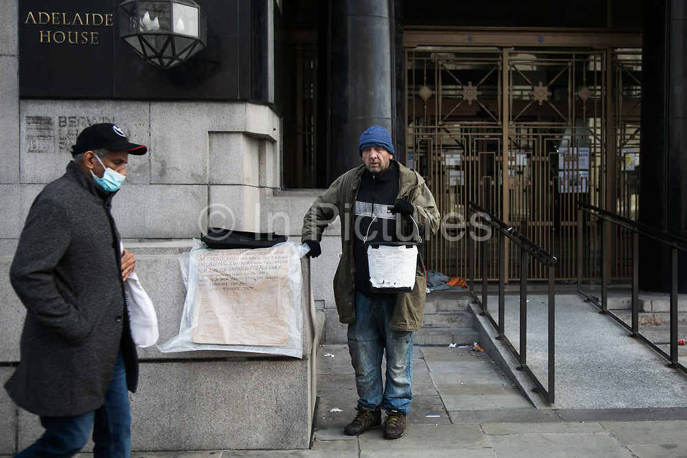 Jeff is homeless and begging for cash on London Bridge on the first day of the national lockdown on 5th of Novemebr 2020, central London, United Kingdom. Jeff has slept in the door way behind and he needs money to feed himself. Not many people have passed or stop to help. Jeff has been homeless for many years and coronavirus and lockdown is only making his life more difficult. The UK Govenrment introduced a 4 week lockdown from November 5th - December 2nd to combat the cororanavirus outbreak.