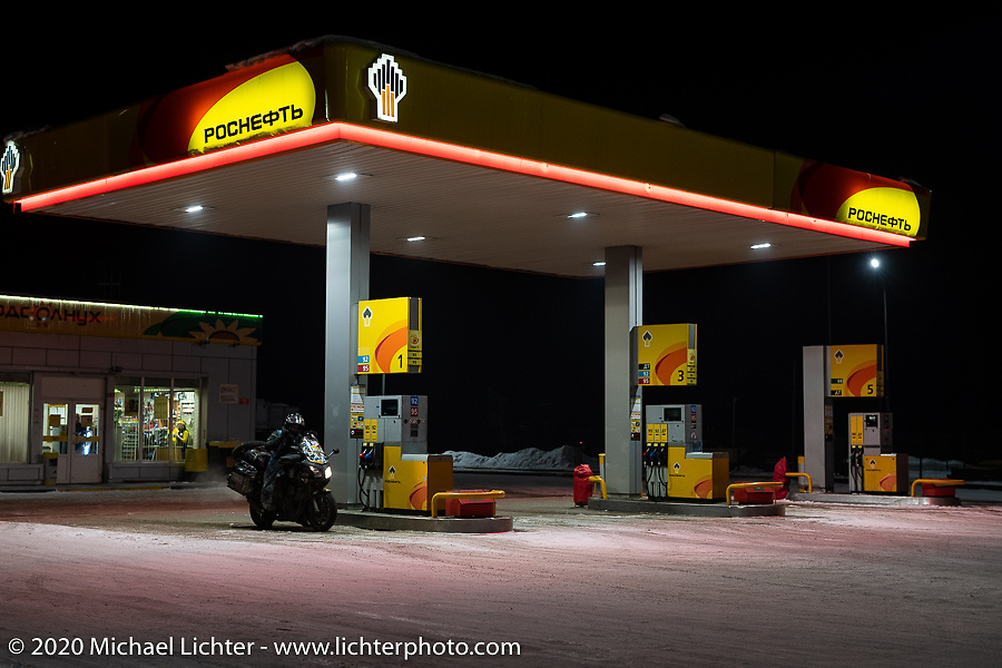 Alessandro Ciceri, known for his cold weather riding and as Wizz on social media (@wizz_inwiaggio), had already ridden 6,200 miles (10,000 km) from his home in Italy in the middle of winter and raced on the mile long ice track by this point. Here he is at a gas station 40 km from Ulan-Ude in 6 degree F weather (-14.4 C) just before riding up a snowy mountain pass at night with another 3,100 miles (5,000 Km) to go through Siberia to Vladivostok after the Baikal Mile Ice Speed Festival. Maksimiha, Siberia, Russia. Monday, March 2, 2020. Photography ©2020 Michael Lichter.