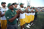A group of Green Bay Packers ;players and coaches clap in support during the announcement canceling the 2016 NFL Pro Football Hall of Fame preseason football game against the Indianapolis Colts on Sunday, Aug. 7, 2016 in Canton, Ohio. The game was canceled for player safety reasons due to the condition of the paint on the turf field. (©Paul Anthony Spinelli)