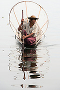 Myanmar, (Burma), Inle Lake, a man is in a canoe with his conical bamboo fishing next