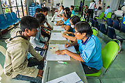 09 JULY 2014 - ARANYAPRATHET, SA KAEO, THAILAND: A Thai immigration officials (right) help Cambodian migrant workers through the process of registering for an ID card at the Thai Immigration One Stop Service Center in Aranyaprathet on the Thai-Cambodian border. More than 200,000 Cambodian migrant workers, most undocumented, fled Thailand in early June fearing a crackdown by Thai authorities after a coup unseated the elected government. Employers have been unable to fill the vacancies created by the Cambodian exodus and the Thai government has allowed them to return. The Cambodian workers have to have a job and their employers have to vouch for them. The Thai government is issuing temporary ID cards to allow them to travel openly to their jobs. About 800 Cambodian workers came back to Thailand through the Aranyaprathet border crossing Wednesday. The Thai government has opening similar service centers at three other crossing points on the Thai-Cambodian border.    PHOTO BY JACK KURTZ