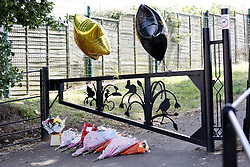 © Licensed to London News Pictures.16/07/2013. Soth Yardley, Birmingham, UK. The scene in Wash Lane, South Yardley, Birmingham, where a fifteen year old boy was stabbed at the entrance to the nearby park. Pictured, floral tributes.  Photo credit : Dave Warren/LNP