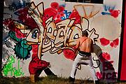 Graffiti artist painting a mural in the centre of Shangri-La, Glastonbury Festival 2010