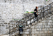 Young girl and dog ascend stairs, Dubrovnik old town, Croatia