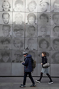 People walking past a large metal wall depicting the faces of various comedians and entertainers in London, United Kingdom.