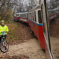 Bicycle rider watches the Children's Railway pass by in a forest in the Buda Hills in Budapest, Hungary on November 16, 2014. ATTILA VOLGYI