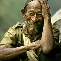 A village elder rests beside the trail in the Kali Gandaki Valley, Nepal.