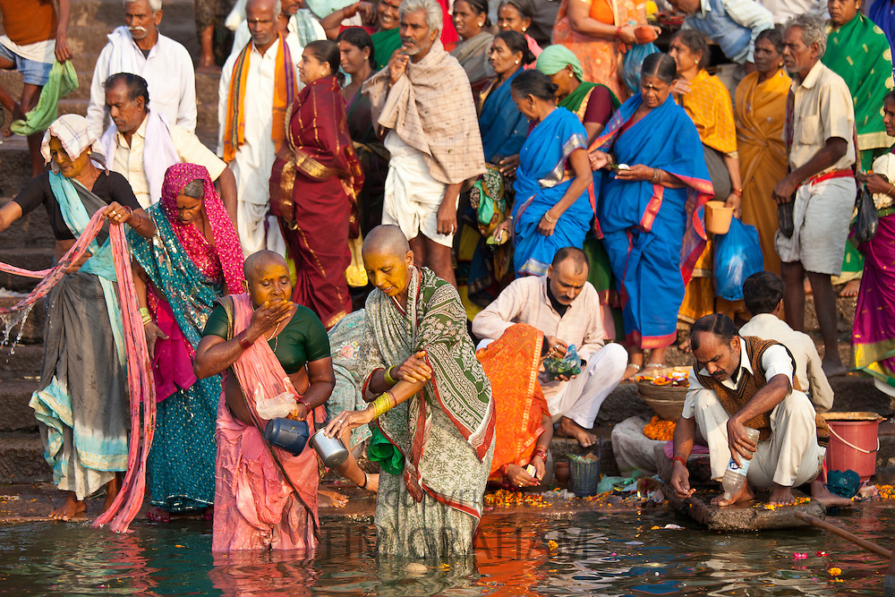 Indian Hindu pilgrims bathing and cleaning teeth in The Ganges River at Dashashwamedh Ghat in Holy City of Varanasi, India