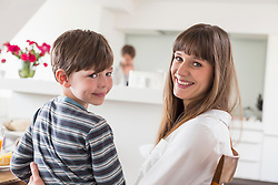 Portrait of mother and son smiling while man in background