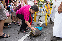 © Licensed to London News Pictures. 28/09/2014. Ipoh, Malaysia. A woman strokes a tortoise from a temple for luck as devotees process with deities through the streets of central Ipoh, Malaysia on the 5th day of the Nine Emperor Gods Festival, Sunday, Sept. 28, 2014. The festival is a nine-day Taoist celebration to mark the birth of the Nine Emperor Gods from the first day to the ninth day of the ninth moon in Chinese Lunar Calender. The origin of the Nine Emperor Gods (stars of the Northern constellation) can be traced back to the Taoist worship of the Northern constellation during Qin and Han Dynasty and absorb this practice of worshipping the stars and began to deitify them as Gods. Photo credit : Sang Tan/LNP