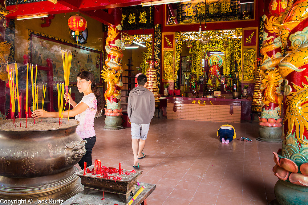 """12 APRIL 2012 - HO CHI MINH CITY, VIETNAM:  People pray in the entry way of Chùa Quan Âm (Avalokiteshvara Pagoda), a Chinese style Buddhist pagoda in Cho Lon. Founded in the 19th century, it is dedicated to the bodhisattva Quan Âm. The pagoda is very popular among both Vietnamese and Chinese Buddhists. Cholon is the Chinese-influenced section of Ho Chi Minh City (former Saigon). It is the largest """"Chinatown"""" in Vietnam. Cholon consists of the western half of District 5 as well as several adjoining neighborhoods in District 6. The Vietnamese name Cholon literally means """"big"""" (lon) """"market"""" (cho). Incorporated in 1879 as a city 11km from central Saigon. By the 1930s, it had expanded to the city limit of Saigon. On April 27, 1931, French colonial authorities merged the two cities to form Saigon-Cholon. In 1956, """"Cholon"""" was dropped from the name and the city became known as Saigon. During the Vietnam War (called the American War by the Vietnamese), soldiers and deserters from the United States Army maintained a thriving black market in Cholon, trading in various American and especially U.S Army-issue items.       PHOTO BY JACK KURTZ"""
