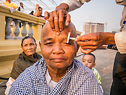 """31 JANUARY 2013 - PHNOM PENH, CAMBODIA:  A Cambodian woman has her eyebrows shaved off after shaving her head while mourning the death of former Cambodian King Norodom Sihanouk. In Cambodia, the spouse and the children mourn the death of their husband or father by shaving their heads, and many Cambodian women have shaved their heads recently because Sihanouk was revered as the father of the nation. Norodom Sihanouk (31 October 1922- 15 October 2012) was the King of Cambodia from 1941 to 1955 and again from 1993 to 2004. He was the effective ruler of Cambodia from 1953 to 1970. After his second abdication in 2004, he was given the honorific of """"The King-Father of Cambodia."""" Sihanouk served two terms as king, two as sovereign prince, one as president, two as prime minister, as well as numerous positions as leader of various governments-in-exile. He served as puppet head of state for the Khmer Rouge government in 1975-1976. Most of these positions were only honorific, including the last position as constitutional king of Cambodia. Sihanouk's actual period of effective rule over Cambodia was from 9 November 1953, when Cambodia gained its independence from France, until 18 March 1970, when General Lon Nol and the National Assembly deposed him. Upon his final abdication, the Cambodian throne council appointed Norodom Sihamoni, one of Sihanouk's sons, as the new king. Sihanouk died in Beijing, China, where he was receiving medical care, on Oct. 15, 2012. His funeral procession, which will wind through Phnom Penh is Friday, Feb.1 and his cremation is on Feb. 4, 2013. Over a million people are expected to attend the service.    PHOTO BY JACK KURTZ"""