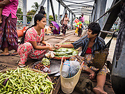 08 JUNE 2014 - YANGON, MYANMAR: A vegetable vendor on a pier on the Yangon waterfront. Yangon, Myanmar (Rangoon, Burma). Yangon, with a population of over five million, continues to be the country's largest city and the most important commercial center.      PHOTO BY JACK KURTZ