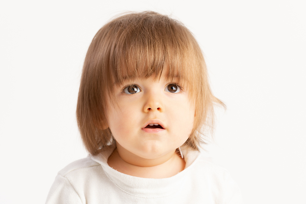 Close-up of a 1 year old baby boy with a Surprised face expression on white background.