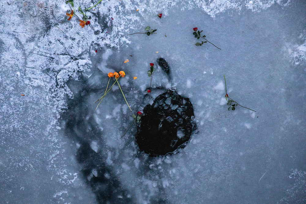 A hole in the ice where the carcass of a swan lay for several days in the frozen Landwehr Canal in Berlin, Germany, February 13, 2021. It appears people scattered flowers from a bridge above the frozen canal. Germany is experiencing extreme winter weather as part of a polar vortex, with temperatures going well beneath freezing.