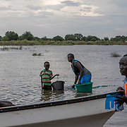 A UNICEF boat approaches a now displaced community  of 7,000, on 6 November 2019, after flooding destroyed their homes in Pibor, Boma State, South Sudan. The population must use the contaminated flood water for all of their needs including laundry, cooking and bathing.  // Photo credit: UNICEF South Sudan/de la Guardia
