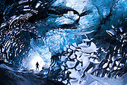 January 12 - Lone explorer can be seen passing through one of the gateways to Iceland, an ice cave located in Vatnajökull glacier.<br /> <br /> <br /> The Gateway to Iceland. An ice cave in Vatnajökull ice cap, south Iceland