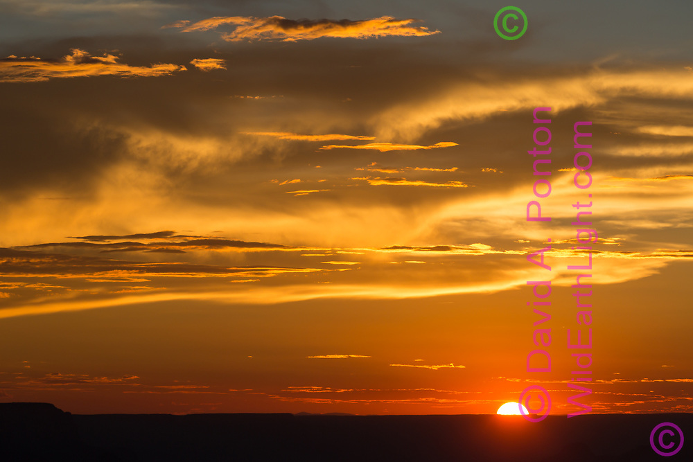 Setting sun halfway behind the horizon of the Kaibab Plateau at the Grand Canyon, with yellow and orange light in dramatic clouds, America, © David A. Ponton