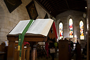 An open Christian Bible in the interior of St. Mary's church on Holy Island, on 27th September 2017, on Lindisfarne Island, Northumberland, England. The Holy Island of Lindisfarne, also known simply as Holy Island, is an island off the northeast coast of England. Holy Island has a recorded history from the 6th century AD; it was an important centre of Celtic and Anglo-saxon Christianity. After the Viking invasions and the Norman conquest of England, a priory was reestablished.