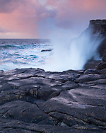 A large wave breaks on the rocks at Reiff in Assynt, Scotland, at sunset lights up the clouds behind.