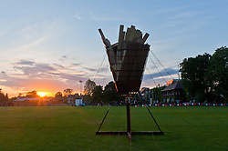 © Licensed to London News Pictures. 04/06/2012. London, UK.  An unlit Jubilee Beacon at Kings College School, Wimbledon, London.  The beacon  sits in the cricket grounds of the school waiting to be lit, the sun sets as local people celebrate over a barbeque.  The beacon is part of a network of over 4000 lit by communities and others throughout the United Kingdom, Channel Islands and the Isle of Man, along with the Commonwealth.  The Royal Jubilee celebrations. Great Britain is celebrating the 60th  anniversary of the countries Monarch HRH Queen Elizabeth II accession to the throne this weekend.  Photo credit : Richard Isaac/LNP