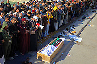 Pro-rebel supporters pray over the body of a fighter killed on 22 March in ongoing fighting for the city of Ajdabiyah, 140km from Benghazi in eastern Libya