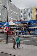 An elderly couple walk past the new development and the ageing Elephant and Castle shopping centre, on 29th March, 2018 in London, England.