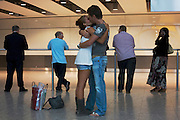 Amid the hectic arrivals concourse of Heathrow airport's T5, a young couple kiss and embrace after a few weeks separation.