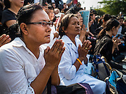 16 DECEMBER 2015 - BANGKOK, THAILAND: Women pray during the funeral for Somdet Phra Nyanasamvara, Thailand's Supreme Patriarch, during the Patriarch's funeral. He died Oct. 24, 2013. He was ordained as a Buddhist monk in 1933 and appointed as the Supreme Patriarch in 1989. He was the spiritual advisor to Bhumibol Adulyadej, the King of Thailand when the King served as a monk in 1956. Tens of thousands of people lined the streets during the procession to pray for the Patriarch.     PHOTO BY JACK KURTZ