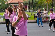 07 JULY 2011 - BANGKOK, THAILAND:   Women do Tai-Chi early in the morning in Lumpini Park. Lumphini Park (also Lumpini or Lumpinee) is a 360-rai (57.6-hectare or 142-acre) park in Bangkok, Thailand. The park offers open public space, trees and playgrounds in the Thai capital and contains an artificial lake where visitors can rent a variety of boats. Paths around the park totalling approximately 2.5 km in length are a popular area for evening joggers. Lumpini Park was created in the 1920s by King Rama VI on royal property. A statue of the king stands at the southwestern entrance to the park. It was named for Lumbini, the birthplace of the Buddha in Nepal, and at the time of its creation stood on the outskirts of the city. Today it lies in the heart of the main business district and is in the Lumphini sub-district, on the north side of Rama IV Road, between Ratchadamri Road and Witthayu (Wireless) Road.   PHOTO BY JACK KURTZ